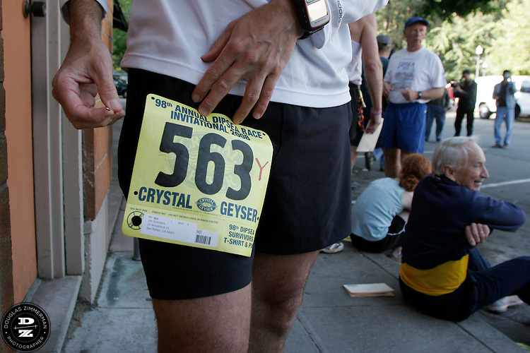 Jim Schollard of San Rafael, Calif. (563)  places his racing bib on in downtown Mill Valley before the 98th running of the Dipsea Race from Mill Valley, Calif. to Stinson Beach over Mt. Tamalapais.  The race happened on Sunday, June 8, 2008.