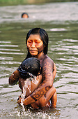A-Ukre, Xingu, Para State, Amazon, Brazil. A Kayapo Indian woman bathing her child in the river.