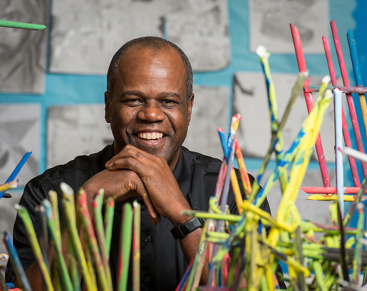Wheatley High School art teacher Lionel Lofton poses for a photograph with student projects, January 29, 2015.