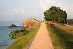 Tourists walk on fort ramparts in historic town of Galle, Sri Lanka, Asia