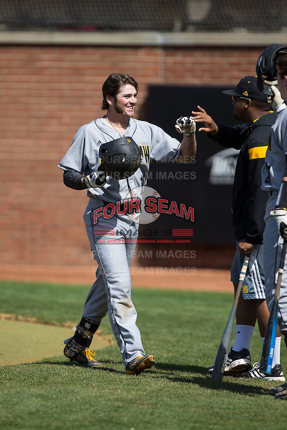 Kal Simmons (10) of the Kennesaw State Owls is congratulated by teammates after hitting a solo home run in the top of the first inning against the Winthrop Eagles at the Winthrop Ballpark on March 15, 2015 in Rock Hill, South Carolina.  The Eagles defeated the Owls 11-4.  (Brian Westerholt/Four Seam Images)