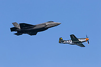 F-35 Lightning II fifth generation fighter flies in formation with a P-51 Mustang first generation fighter as part of the Heritage Flight during the 2019 San Francisco Fleet Week airshow.