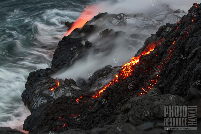 Lava flows down a perilous cliff onto a lava bench on a black sand beach, Hawai'i Volcanoes National Park and Kalapana border, Big Island.