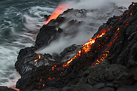 Lava flows down a perilous cliff onto a lava bench on a black sand beach, Hawai'i Volcanoes National Park and Kalapana border, Big Island.