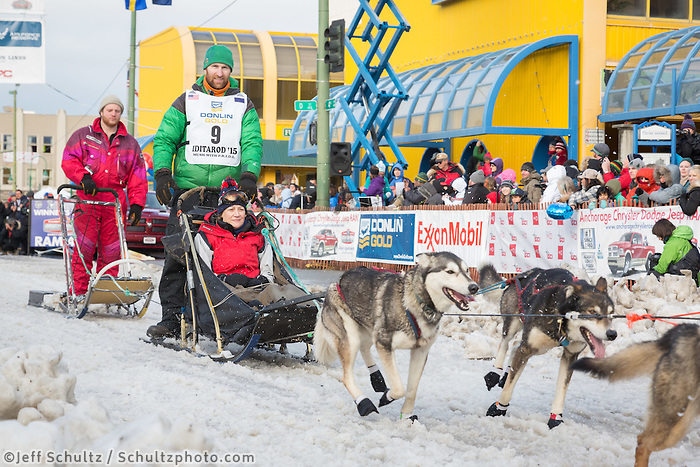 Kelly Maixner and team leave the ceremonial start line with an Iditarider at 4th Avenue and D street in downtown Anchorage, Alaska during the 2015 Iditarod race. Photo by Jim Kohl/IditarodPhotos.com