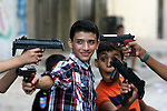 Palestinian boys play with toy guns to celebrate Eid al-Fitr during the second day of the holiday of Eid al-Fitr marking the end of Islam's fasting holy month of Ramadan, in Rafah in southern in Gaza cityon Aug. 09, 2013. Muslims around the world are celebrating Eid al-Fitr this week, marking the end of holiest month of Ramadan during which followers are required to abstain from food, drink and sex from dawn to dusk. Photo by Eyad Al Baba