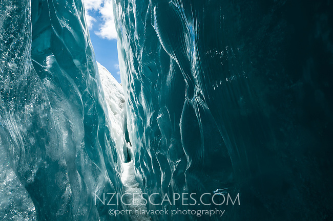 Walking through dark green, beautifully textured, glass like looking crevasse on Franz Josef Glacier, Westland Tai Poutini National Park, UNESCO World Heritage Area, West Coast, New Zealand, NZ