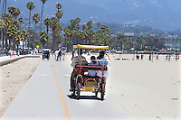 Family in a Deuce Coupe peddle bicycle on the promenade at Santa Barbara beach California