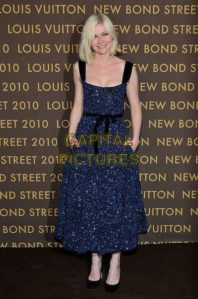 KIRSTEN DUNST .attends the launch of the Louis Vuitton Bond Street Maison in London, England, UK, May 25th, 2010. .full length cleavage black straps sash belt waist blue print dress hands in pockets shoes sleeveless .CAP/PL.©Phil Loftus/Capital Pictures.