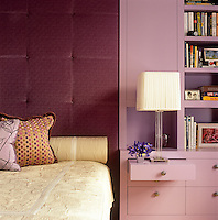 In a bedroom of a New York apartment the floor-to-ceiling padded headboard of the double bed is covered in lilac velvet with adjacent built-in cupboards and shelving painted in a co-ordinating tone