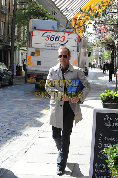 KIEFER SUTHERLAND.Spotted shopping at a women's underwear shop in Covent Garden, London, England..April 21st, 2010.full length  black blue trousers cardigan jumper beige trenchcoat jacket sunglasses aviators shades blue box parcel walking.CAP/IA.©Ian Allis/Capital Pictures.
