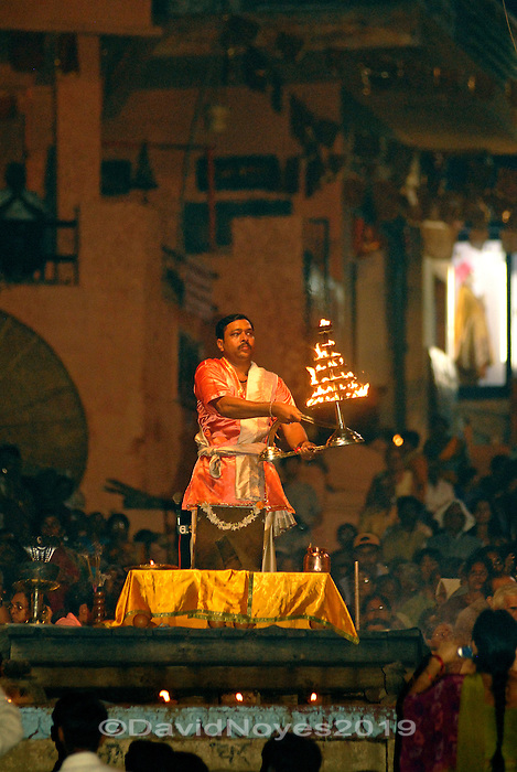 At the Dashashwamedh ghat in Varanasi  a mass of faithful  gather for the nightly Aarti ceremony. A Hindu priest raises and lowers a glowing offering of open flames as the sounds of bells, chanting, and hypnotic song washed over the crowd from unseen loudspeakers..