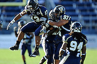 27 November 2010:  FIU's Toronto Smith (13), Jose Cheeseborough (27), Tourek Williams (97) and James Jones (94) celebrate a defensive stop in the first quarter as the FIU Golden Panthers defeated the Arkansas State Red Wolves, 31-24, at FIU Stadium in Miami, Florida.