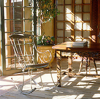 In the living room of a house in Cape Town an antique wrought-iron rocking chair has been placed to catch the breeze through the open French windows
