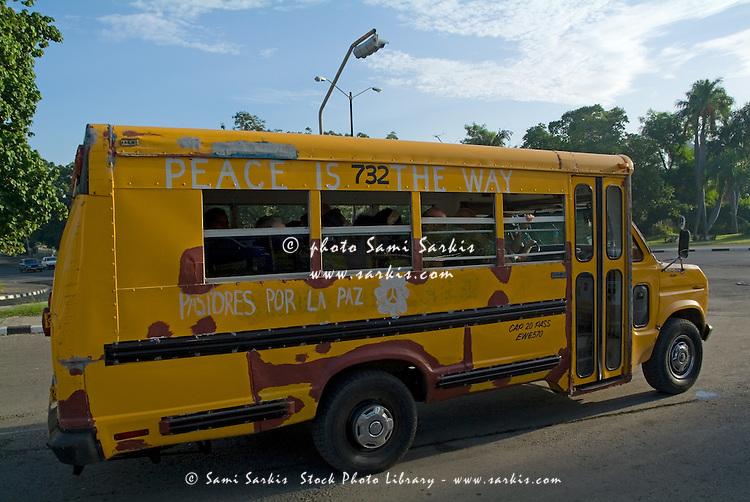 Yellow bus bearing the slogan 'Peace is the way', in Havana, Cuba.