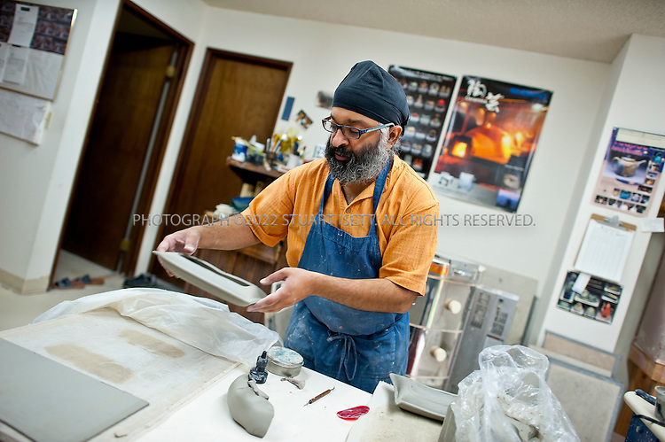 8/2/2011--Federal Way, WA, USA..Charan Sachar, 37, left his job as a computer programmer/software engineer to open his own online pottery shop, Creative With Clay. He lives in  Federal Way, Washington (30 miles south of Seattle) and works in a home studio shown here...©2011 Stuart Isett. All rights reserved.