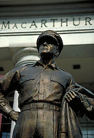 Detail view of the brass statue of General MacArthur at the MacArthur Memorial, with its main building visible in the background. Norfolk Virginia, MacArthur Memorial.
