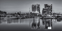A new day begins in Baltimore with part of the skyline of the Harbor East development, including the Baltimore Marriott Waterfront Hotel and the Legg Mason Building, reflected in the still waters of the Patapsco River during the last hour before sunrise.