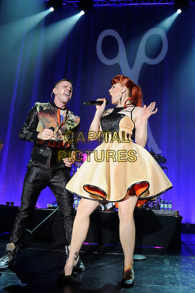 Jake Shears and Ana Matronic.Scissor Sisters performing live in concert, Camden Roundhouse, London, England. .23rd October 2012.on stage gig performance performing music full length black trousers orange green print jacket dancing yellow dress singing profile .CAP/MAR.© Martin Harris/Capital Pictures.