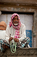 A man performing his morning meditation and repeating his mantra 108 times while he counts with his mala. Varanasi, India, Asia.