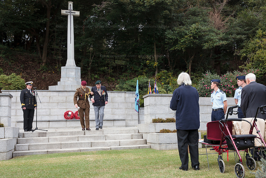 Ex-Japanese prisoner of War, Roy Welland (94) is helped down the steps of the Cross of Sacrifice after laying a wreath during the Remembrance Day ceremonies at the Commonwealth War Cemetery in Hodogaya, Yokohama, Japan. Wednesday November 11th 2015 Roy Welland is from Colchester in Essex and served with the Royal Berkshire regiment in India in WW2