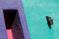 Wall lamp on turquoise wall in colorful La Placitas Village.