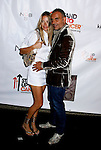 Fashion designer Christian Audigier (R) and wife Ira arrive at the launch of Camila Alves' Handbag Collection MUXO at Kitson Studio on August 7, 2008 in Los Angeles, California.