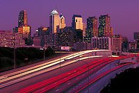 Light streaks of I 76 are the foreground of a golden sunset skyline. Philadelphia Pennsylvania United States skyline.