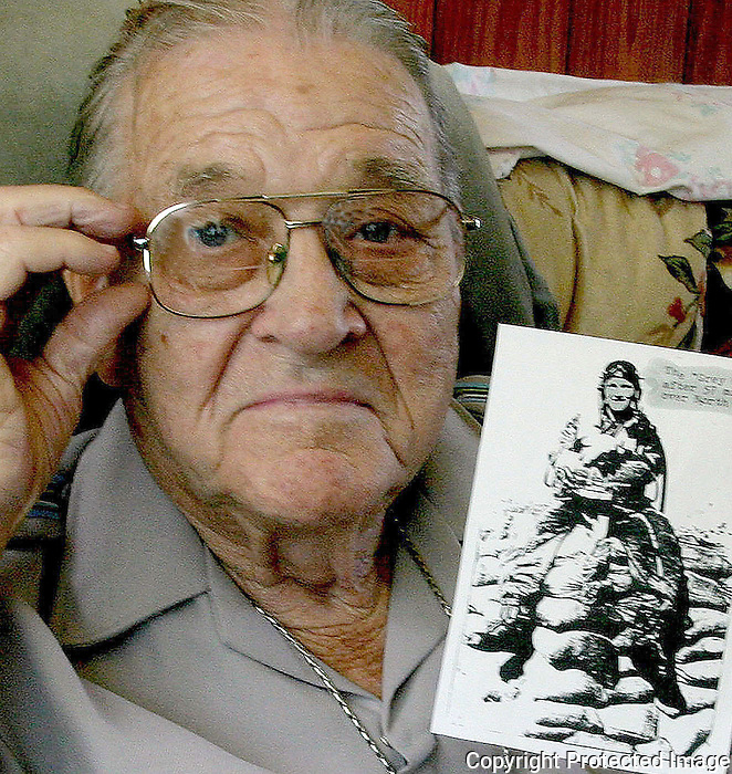 07/28/04...Gary Wilcox/staff.....Frank Grey holds a photo of himself taken after he had 57 missions over North Korea.