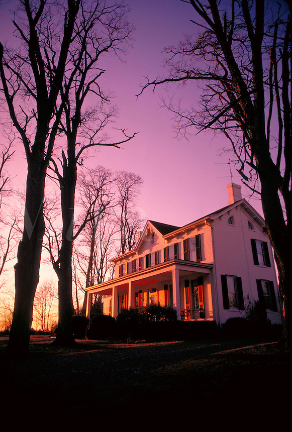 Trees reach over this country mansion. Orange and purple sunset. United States farm.
