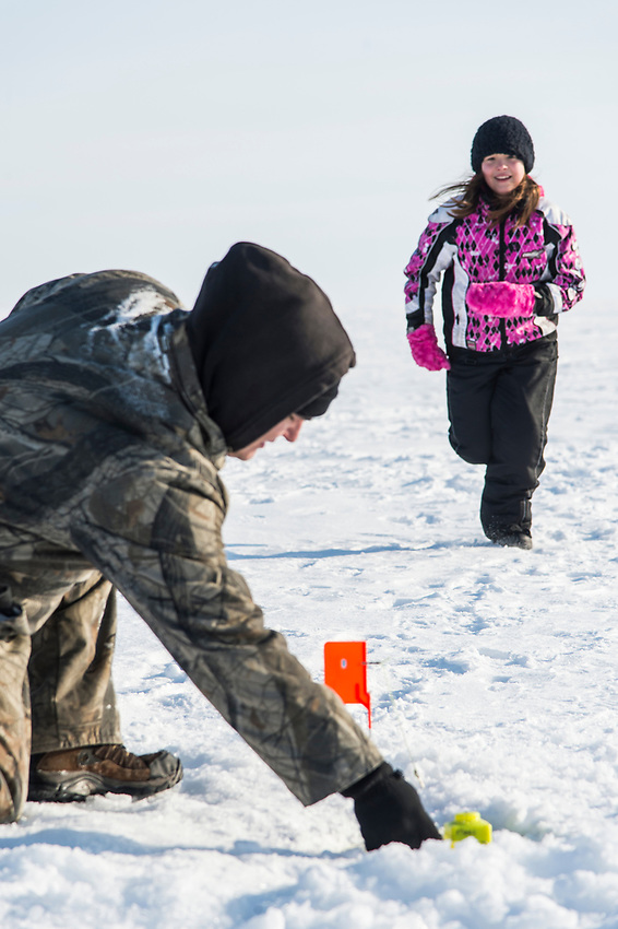 A Native American family ice fishes and plays on frozen Little Bay de Noc near Gladstone, Michigan.