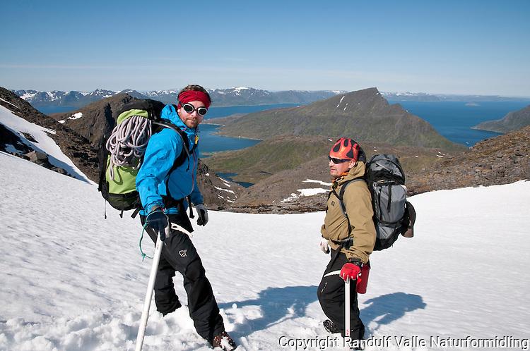 To personer på snøfelt mot Engerdalvatnet på Seiland. Stortinden ved Kårhamn øverst i midten. ----- Two people decending a snow field on Seiland.