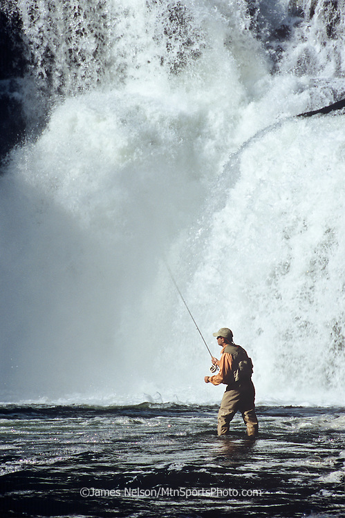 089489C. An angler casts a fly for trout at the base of Lower Mesa Falls on the Henry's Fork, Idaho.