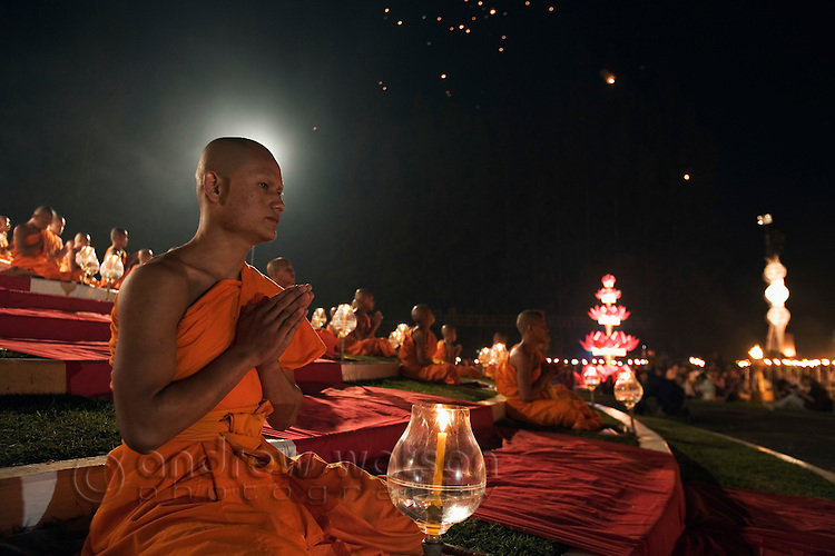 Monks sit in prayer during Yi Peng celebrations at San Sai - part of the annual Loi Krathong festival.  San Sai, Chiang Mai province, THAILAND.