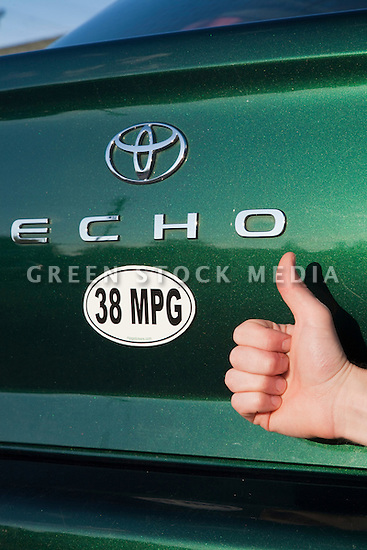 Close up of a person holding thumbs up next to a 38 miles per gallon fuel efficiency bumper sticker on a green Toyota Echo car. Sticker from MPG Stickers (mpgstickers.com), a grassroots, nonprofit campaign which aims to accelerate the adoption of fuel efficient vehicles in the United States. California, USA. Property released from mpgstickers.com.