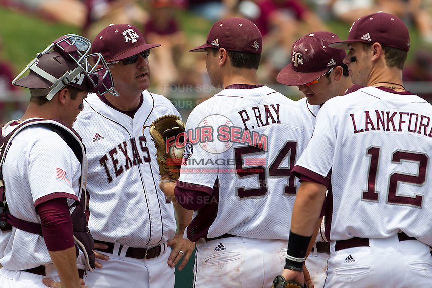 Texas A&M Aggies coach Rob Childress (29) talks on the mound to pitcher Parker Ray (54) during the game against the LSU Tigers in the NCAA Southeastern Conference on May 11, 2013 at Blue Bell Park in College Station, Texas. LSU defeated Texas A&M 2-1 in extra innings to capture the SEC West Championship. (Andrew Woolley/Four Seam Images).