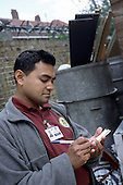 Bethnal Green Neighbourhood Warden  Doraj Miiah makes a  report on illegally dumped rubbish in a Tower Hamlets back street