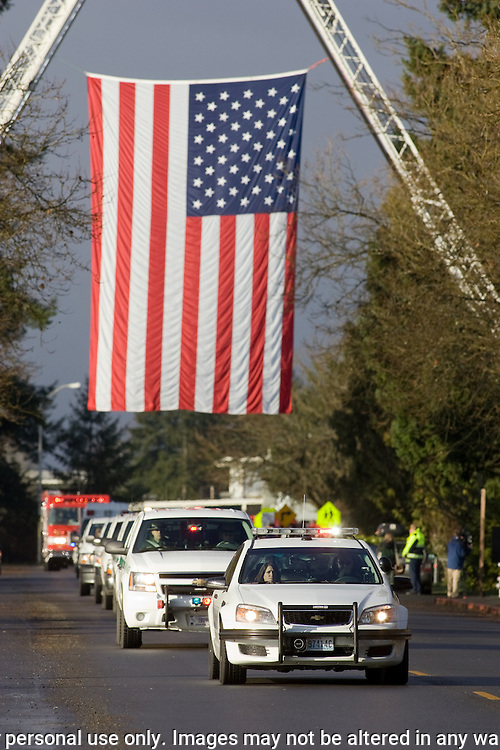National Park Service vehicles drive underneath a U.S. Flag during memorial services for National Park Service Ranger Margaret Anderson at the Pacific Lutheran University in Tacoma on January 10, 2010.  Anderson, was slain at Mount Rainier on New Years' Day when she set up a road block to intercept a vehicle, driven by Benjamin Barnes, who failed to stop at a chain-up checkpoint.  Barnes, the suspect  in the shooting was found dead was found dead the next day. He had drown in Paradise Creek.    ©2012. Jim Bryant Photo. All RIGHTS RESERVED.