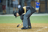 Home plate umpire Adam Clark cleans home plate during the Appalachian League game between the Kingsport Mets and the Burlington Royals at Burlington Athletic Stadium on July 27, 2018 in Burlington, North Carolina. The Mets defeated the Royals 8-0.  (Brian Westerholt/Four Seam Images)