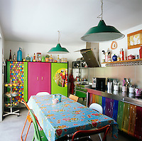 The white walls of the kitchen set off the brightly coloured cabinets and table and chairs.