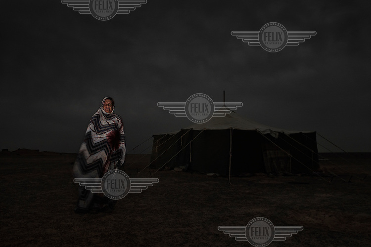 Mainaha Brahim Bahaha, 64, Bedouin woman. Pictured at her home in Mehaires, in Polisario controlled Western Sahara (Saharawi Arab Democratic Republic): 'I was born in Mijek in 1945. I grew up in the desert with the animals and we were all the time moving. If we heard it was raining somewhere we would move. Everything was packed on the camels and we also rode them to the new place. After 1963 we got a car, it was not hard we just sold a few camels and bought it from Trans-Sahara. It changed life for us. Cars were very fast and we could pack a lot of things inside so it was very easy for us to move. But the camel is still the most important thing for the Bedouin. The car allows us to get things from the far away cities, like clothes, oil, flour and sugar but the milk and meat from the camel is how we survive.'.
