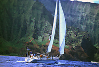 Family sailing a 48 foot sailboat down the rugged Na Pali Coast, Kauai, Hawaii