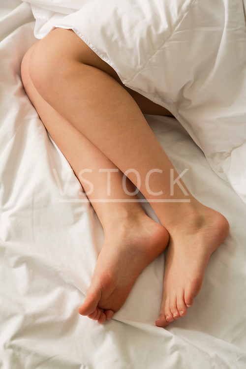 High angle view of female bare legs in white bedding