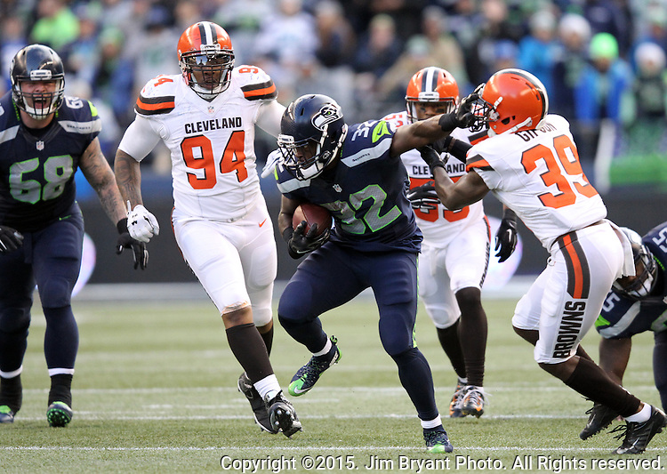 Seattle Seahawks running back Christian Michael stiff arms Cleveland Browns defensive back Tashaun Gipson (39) at CenturyLink Field in Seattle, Washington on December 20, 2015. The Seahawks clinched their fourth straight playoff berth in four seasons by beating the Browns 30-13.  ©2015. Jim Bryant Photo. All Rights Reserved.