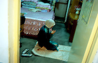 CHINA. Beijing. A Muslim woman prays in her bedroom at home. 2005