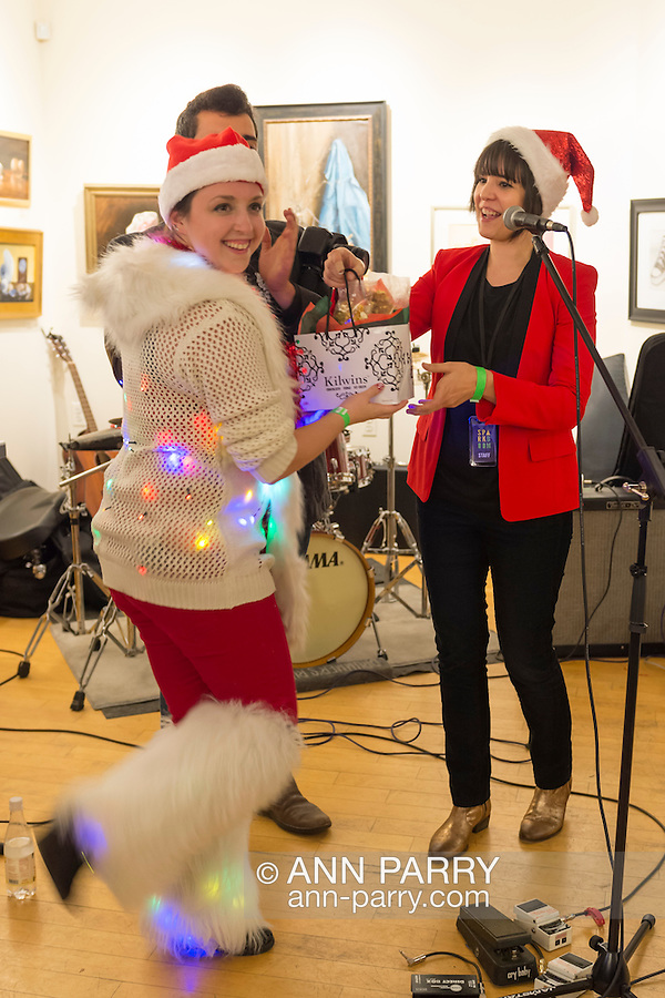 Huntington, New York, USA. February 20, 2014. MEREDITH NUSSBAUM, wearing a fuzzy white sweater and leggings decorated with twinkling Christmas lights, wins a prize for her creative 'Ugly Sweater' at The Jingle Boom Holiday Bash, at the Main Street Gallery of Huntington Arts Council. Sparkboom, an HAC project, provides events such as this geared to Gen-Y, 18-34 years of age, to address the 'brain drain' of creative young professionals of Long Island. The paintings on the art gallery walls were the Annual Juried Still Life Show.