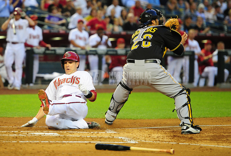 Apr. 17, 2012; Phoenix, AZ, USA; Arizona Diamondbacks base runner Miguel Montero slides safely into home ahead of the throw to Pittsburgh Pirates catcher Rod Barajas in the first inning at Chase Field.Mandatory Credit: Mark J. Rebilas-
