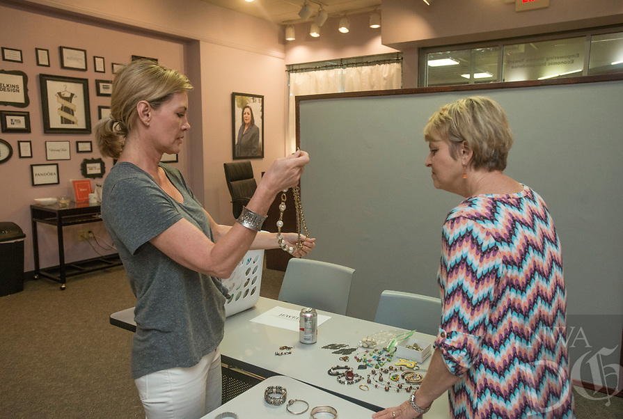 NWA Democrat-Gazette/BEN GOFF @NWABENGOFF<br /> Kate Butler (left) of Bentonville and Gwen Shankle of Springdale volunteer Saturday, Aug. 4, 2018, during a 'Suit Sorting Saturday' at Dress for Success Northwest Arkansas in Frisco Station Mall in Rogers. Dress for Success, with an additional boutique in Springdale, helps empower women entering the workforce by providing support, classes and appropriate professional attire free of charge. Their clients are referred to them from other area organizations, and include women trying to overcome poverty, new citizens and those returning to society after being incarcerated. Volunteers gather once a month at the Rogers location for a Suit Sorting Saturday to help with intake, sorting, cleaning and repair of donated clothing. The organization plans to hold their annual inventory reduction sale Aug. 25., which is open to the general public and helps fund the organization.