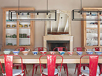 Red metal Tolix chairs by Xavier Pauchard are arranged around a table in a spacious dining room. Two glass fronted pine display cabinets stand either side of a French Louis XVI fireplace. Two contemporary Nautic pendant lights by Lampe Gras hang above the table.