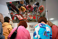 Visitors are reflected in an overhead mirror during the San Diego Book Arts ninth annual Edible Book Tea at the Watercolor Society Gallery, NTC Pomenade, Liberty Station, San Diego, California Saturday, April 5, 2008.  The event featured books made from edible materials amd prizes were award to the best entrants.